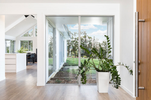 entranceway, wood front door, indoor plant, white living area, white house