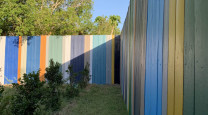 This artist's Brisbane home is so colourful even the 85m fence is an elegant rainbow photo